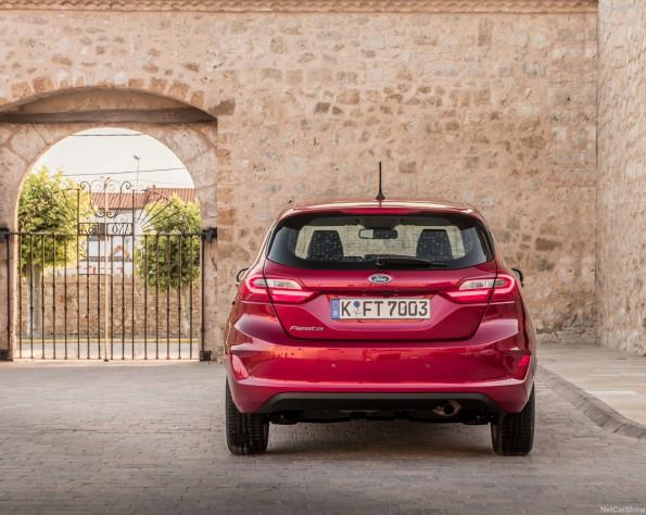Achterkant rode Ford Fiesta met op de achtergrond een muur