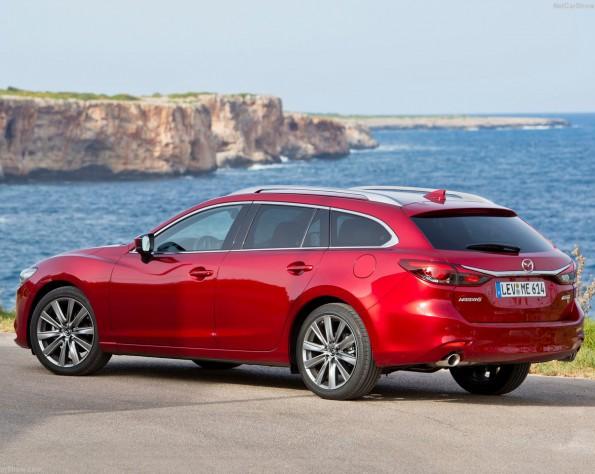 Mazda 6 zijkant schuin met uitzicht op zee